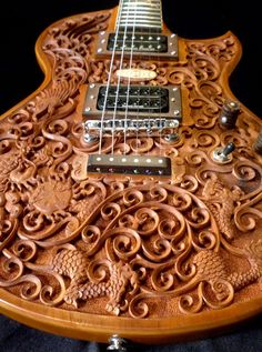 An intricately carved solid mahogany electric guitar with 'Hawk & Dragon' motif. Hand-made in Montreal by artists of Blueberry Musical Instruments, Inc.