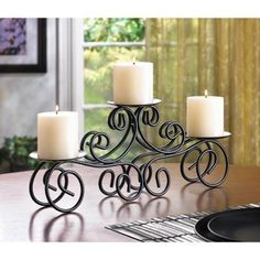 Tuscan Candle Centerpiece For instant decorating magic, look no further than this curvy candle stand! Elegantly fashioned from wrought iron scrolls, this triple-candle decoration makes a gracious focal point atop your mantle, table or shelf. Design Candle Holders, Black Candle Holders, Wrought Iron Candle Holders, Candle Holder Decor, Candle Holders Wedding, Pillar Candle Holders, Pillar Candles, Candleholders, Candle Stands