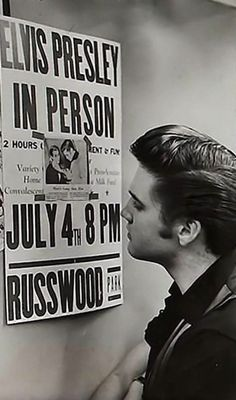 Elvis Presley examining a poster announcing his appearance at Russwood Park, Memphis, TN.