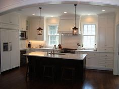 White perimeter cabinets with dark stained island, carerra marble counter tops, white subway tile back splash, and built-in refrigerator.