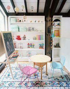 playroom for kids. Funky oloured chairs and black board and lovely big book case and rug