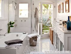 Master Bathroom  A neutral palette with hints of gray give the bath a serene feel. The door lets in abundant light and leads to the pool outside.