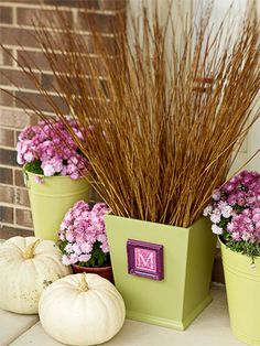 Monogrammed Planter: Make your house feel like a home with planters that call out your family's initial. This planter is actually a painted wooden trash can. The small frame, featuring a clip art letter, is attached with hot glue. A smattering of mums and pumpkins, plus a high-reaching collection of twigs, completes the fall feel.
