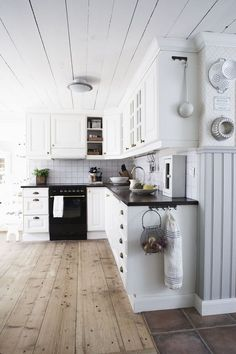 Warm wood floors, white cabinets, black countertops, black hardware