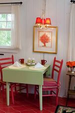 sage green table with red chairs.