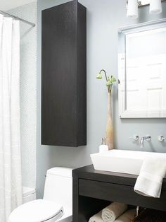 Employ the wall space above your toilet for storage. Hang a cabinet above the toilet and use it to store extra toilet paper, linens or toiletries. Pick up a single cabinet at an architectural salvage or building materials salvage store, such as Habitat for Humanity's ReStore. Paint or refinish the cabinet to match your decor, and mount it on the wall using hardware designed for that purpose.