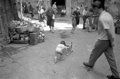 David Seymour ITALY. Naples. 1948. A small child plays at train through a street.