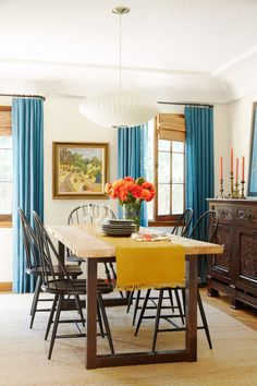 The raw wood farm table and black Windsor chairs in this dining room keep the space from looking to colorful. Such understated supporting players allow the table runner and cerulean blue linen draperies to command attention without overwhelming the eye.