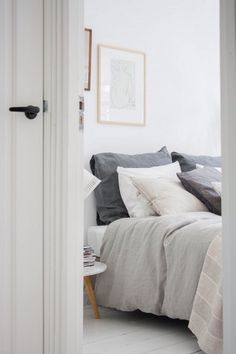 bedroom: glass framed drawings, gray and white linen bedding
