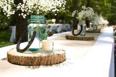 déco mariage champêtre - bocaux en verre bleu avec des gypsophiles sur des rondelles de bois