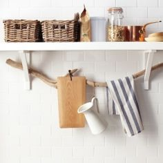 Suspend a branch from shelf brackets for chic storage. Cute, rustic, and practical!