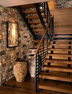 Escada rústica com degraus de madeira, com bases laterais de aço preto corrimão e parede de pedra.