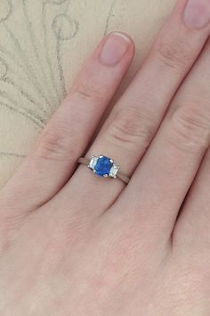 We have a sneak peek for you! This is a new sapphire and diamond engagement ring that will be launching online in a few weeks! Currently this style of ring is available online as a three stone emerald-cut diamond ring. Keep a look out on our Ready to Ship page for the sapphire version to become available. #ThreeStoneRing #SapphireRing #SapphireEngagementRing #BlueSapphire #SapphireandDiamond Vintage Style Engagement Rings, Floral Engagement Ring, Three Stone Engagement Rings, Designer Engagement Rings, Diamond Engagement Rings, Trilogy Engagement Ring, Blue Sapphire Rings, Emerald Cut, Ship