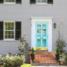 Gray painted brick aqua front door and storm brick steps dentil