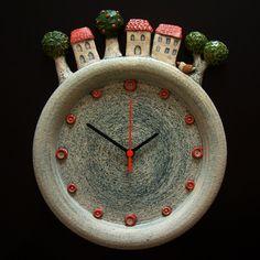 Hodiny s domečky Keramické závěsné hodiny Vyrobeno z hrubé šamotové hlíny, glazováno matnými a lesklými glazurami a engobami. Vyrobené hodiny se mohou mírně lišit v detailech a velikosti. Rozměr 34,5 x 28,5 cm