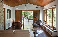 Uma porta larga, de quatro folhas, com vidro e venezianas, foi comprada pronta e faz a ligação entre a sala e a varanda. (Casa.com)
