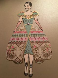 Doll stamps by Character Constructions; tattoo stamp by Something Tattered. Dress constructed with Sizzix die (Rachel Bright) and template by Melanie Muir (sleeves). Die was deconstructed to form pattern pieces and then paper was cut. Paper is by Prima (Madeline).