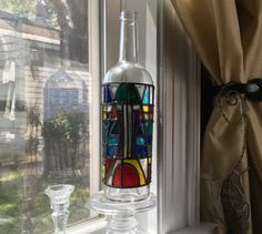 This wine bottle has been up-cycled to give the appearance of stained glass. Its modern design was created and hand painted by me. The bottle stands about 12 inches high, and it looks beautiful in a window with the sun shining through it or on a shelf. If you like the design, but prefer a different color palet, I would be happy to create a custom order. The bottle can be wiped clean with a damp cloth, but it should not be soaked or put in a dishwasher.