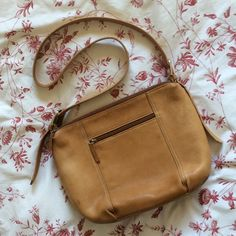 "Tignanello Tan Genuine Leather Crossbody Tan shoulder or crossbody purse in '90s style with attractive curved bottom and lots of pockets! 2 main zip compartments, 2 inner slip pockets, 1 inner zip pocket, 2 outer zip pockets. Genuine leather. Very good used condition with clean interior, slight spots of aging/wear give it character (see pics). Measurements: width at zipper opening 10"" / width at widest point 13"" / width at bottom approx. 10"" / height 8.5"" / depth across bottom 4"" / shortest…"