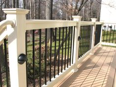 Deckorators Railing and Accessories black aluminum balusters, tan PVC #deck railing, and low voltage accent lighting.