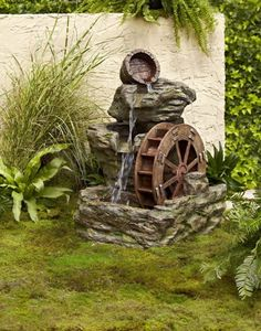 fontaine de jardin design avec une roue et cascade en tonneau et pierres