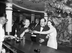 On the up and up Three party-goers raise their glasses at the Cotton Club in 1936 to drink a toast to a bigger and better New Year