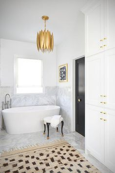 A gold leaf chandelier hangs over a freestanding oval bathtub accented with a floor-mount gooseneck tub filler placed under a window.