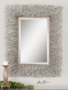 """Mirror has a 1-1/4"""" bevel in a metal hand forged frame that features a champagne highlights and metal finish. Contact us to purchase. 44 W X 56 H X 3 D (in)"""