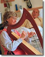 """Therapeutic harpist: Margaret Stephens, a Certified Harp Practitioner, uses music to meet the physical, mental and emotional needs of patients and families in outpatient areas of the cancer center and at the bedside of inpatients. While playing her 23-string harp, Margaret creates a """"cradle of sound"""" to support for the individual's journey of healing (wholeness) and growth."""