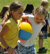 kids running a beachball relay race Ankles tied and carrying a bucket of water across the finish line!