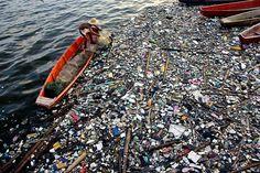 Kalastaja tyhjentää pyydystään muoviroskan täyttämässä vedessä Bulcanissa Filippiineillä.