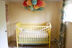 poms and paper lanterns over a crib
