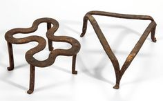 "American wrought iron hearth trivets, comprising a triangular example with three drawn legs and a curvilinear example with four applied legs. Original surfaces. Found in the Shenandoah Valley of Virginia. First half 19th century. 2 1/4"" H, 7"" x 6 1/4"", and 3"" H, 5 1/4"" x 4 3/4""."