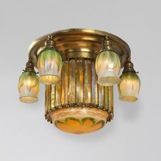 """This unique Tiffany Studios New York Favrile glass and bronze """"Prism"""" ceiling light fixture, featuring a large decorated center glass shade, surrounded by a circular row of grandiose, yet refined, iridescent gold glass """"Prisms."""" Each prism is suspended from a gilt bronze crown, with hanging beaded details. Encircling the shade are six green Favrile glass tulip shades, with pulled-feather decoration, that counter the sleek drama of the prism with a soft form, hue, and delicate decoration. Tiffany Chandelier, Bronze Chandelier, Antique Chandelier, Antique Lighting, Chandelier Pendant Lights, Bubble Chandelier, Crystal Chandeliers, Antique Lamps, Vintage Lamps"""