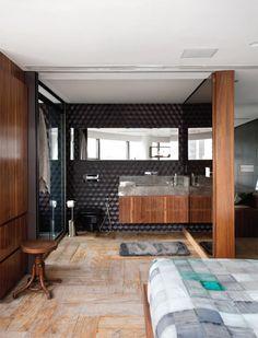 A porta de correr unifca ou isola o banheiro conforme a necessidade. Os tons neutros e masculinos se repetem nos azulejos sextavados da Decortiles e no piso de madeira de demolição.