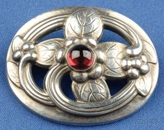 Sterling Silver and Garnet Brooch, Georg Jensen, the flower leaf and vine motif bezel-set with a cabochon garnet, lg. 1 1/2 in., no. 138, signed Georg Jensen Denmark.