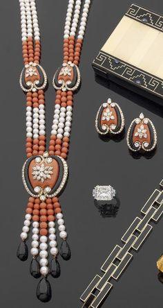CARTIER   Demi-parure comprenant un long collier de perles de culture et de perles de corail ponctuées de motifs de cœurs stylisés d'or jaune, chaque motif de corail et d'onyx bordé et ponctué de diamants ronds, appliqué d'une fleur de diamants navettes. Il est terminé d'une draperie de perles de culture et de corail et de gouttes d'onyx, une paire de clips d'oreilles assortis.   Vers 1970. Signés, numérotés. Dans son écrin de la Maison Cartier.