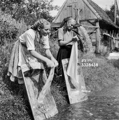 Washing women: circa 1950: Inhabitants of Sestine, Belgrade, in former Yugoslavia, washing clothes on the bank of a river. (