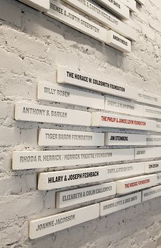 Paula Scher created a dimensional installation that presents donor plaques as bricks that extend from an arrangement in the wall.