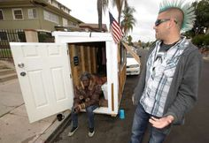 """Los Angeles resident Elvis Summers, right, poses with his tiny house on wheels he built for Irene """"S... - AP Photo/Damian Dovarganes"""