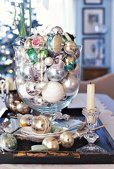 Glass vase filled with vintage Christmas ornaments.