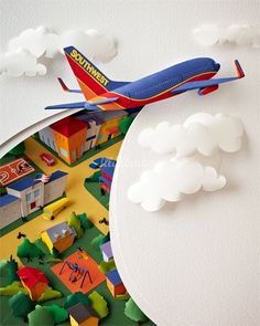 Paper sculpture image of a SouthWest Airlines plane cutting through the sky and clouds: