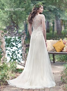 Amal wedding dress by Maggie Sottero   The perfect blend of vintage glamour is found in this elegant Vogue satin, slim A-line slip dress and tulle overlay, with linear patterns of decadent pearls and beading, and a dazzling illusion back. Finished with illusion short sleeves, V-neckline and crystal buttons over zipper closure.
