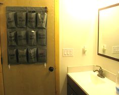 Small Bathroom Organize. Using a shoe over-the-door organizer cut in half, hang it with command adhesive hooks and sharpie to write the labels. No holes... no mess.