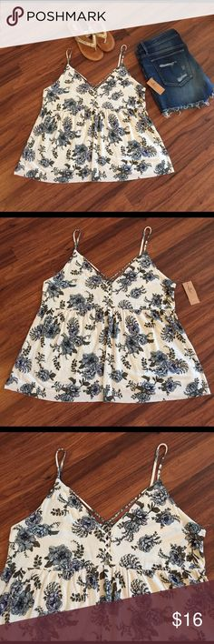 """NWT American Eagle Floral Crepe Top NWT American Eagle Floral Crepe Top. Size XL but can also fit a large! Top features a strap effect in front and a lattice effect down the front and back! Florals are in for summer ladies and this piece is a super cute must have for any closet! Very versatile and can be worn with so many different items! Length: 26"""" Bust: 19.5 Material 94% Viscose (Rayon) and 6% Elastic. American Eagle Outfitters Tops Camisoles"""