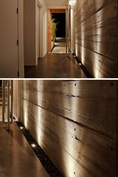 7 Interiors That Use Dramatic Uplighting To Brighten A Space // The strip of pebbles and lights that run along the side of the wall of the entryway in this house uniquely welcome people into the home and helps the texture of the concrete wall stand out.