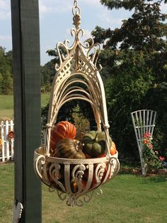 This is a Victorian iron plant hanger that I put fake gourds  pumpkins in it. At Christmas I'm going to put shatterproof ornaments. :-)