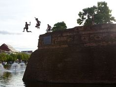 Chiang Mai Summer    Photograph by Palani Mohan    Carefree boys leap from Chiang Mai's old city walls into a cooling moat. The city's walled old center is woven with quiet, narrow lanes.
