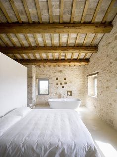 Casa Olivi Old Italian House with Modern Minimalist Interiors : Main Bedroom With Big White Bed And Bathtub Inside