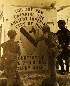 Hue To Go! The battle won, these 5th Battalion, 7th Cavalry, soldiers proclaim their hard-won victory by posting this sign, welcoming other units to Hue.